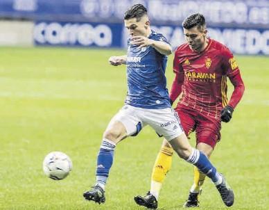 ?? IRMA COLLIN / LA NUEVA ESPAÑA ?? Superado Narváez disputa el balón con el defensa del Oviedo Juanjo Nieto.