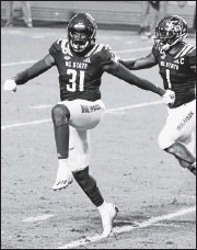 ?? ETHAN HYMAN/THE NEWS & OBSERVER VIA AP ?? North Carolina State's Vi Jones (31) and Isaiah Moore celebrate after Jones blocked a field goal attempt by Liberty's Alex Barbirwith 1: 18 left. TheWolfpack hung on for a 15-14 victory Saturday night in Raleigh, N.C.