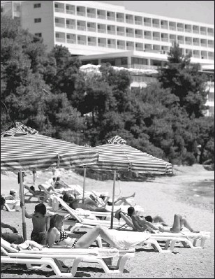 ?? YANNIS KONTOS, BLOOMBERG NEWS ?? Tourists relax by the sea at Club Med in Grecolimano, Greece, yesterday. Club Méditerranée SA, Europe's largest resort operator, has spent $1.5 billion in renovations. All of its properties will boast at least three tridents, the equivalent of the...