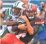 ??  ?? ED MULHOLLAND, USA TODAY SPORTS Browns quarterback Johnny Manziel, right, is hit Sunday by Jets cornerback Buster Skrine.