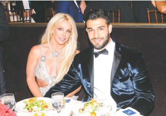 ?? VIVIEN KILLILEA/GETTY IMAGES ?? Singer Britney Spears and actor-personal trainer Sam Asghari, pictured in 2018, announced their engagement on Instagram, which prompted congratulatory and precautionary replies.