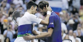 ??  ?? Novak Djokovic and Daniil Medvedev embrace at the net after their men's final match at the US Open Tennis Championships at Arthur Ashe Stadium in New York on 12 September. Photos: Justin Lane/EPA-EFE