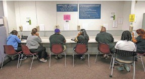 ?? RICH PEDRONCELLI/AP FILE ?? Visitors use the unemployment insurance phone bank in Sacramento, Calif. According to a recent survey, 17% of households reported missing or delaying paying major bills to instead ensure everyone could eat.