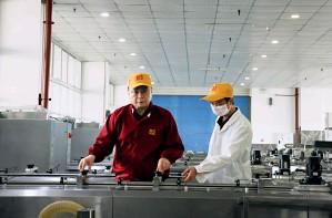 ??  ?? 杨坤龙(左一)视察麻花加工工厂车间