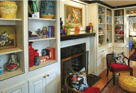 """??  ?? THE PAINTING is paint-by-number, part of a large collection Maggie has. Note how she painted the trim black for contrast against the white bookcases. The chairs on the fireplace are from an estate sale in New Orleans. """"I finally had the right spot for..."""