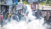 ?? PHOTO: REUTERS ?? Confrontation . . . A man throws a tear gas canister back at police during a protest in PortauPrince, Haiti yesterday.