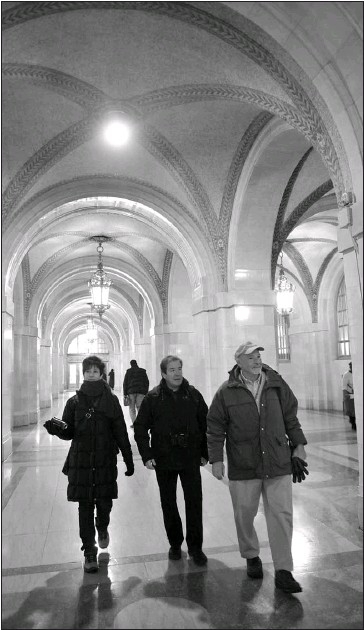 ?? BRIAN JACK­SON~SUN-TIMES PHO­TOS ?? Chicago Greeter John Os­bolt (right) walks Xavier Canas and his wife, Cari Del­gado, through City Hall on the Span­ish cou­ple's re­cent trip to the Windy City.