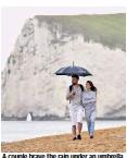 ??  ?? A couple brave the rain under an umbrella on Durdle Door beach in Dorset