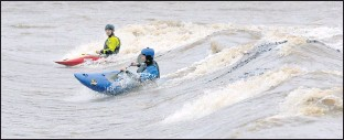 ?? BOB BROWN/TIMES-DISPATCH ?? Tad Dennis (foreground) and Jordan Puffenberger navigated the current in the James River at Z-Dam near Williams Island along Riverside Drive in Richmond on Thursday as heavy rain covered the area.