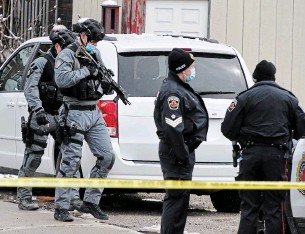 ?? JOHN RENNISON THE HAMILTON SPECTATOR ?? Hamilton police emergency response unit officers appear at the scene of a barricaded man on Barton Street between Sherman and Kinrade avenues Wednesday.