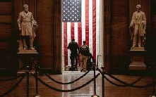?? Erin Schaff / New York Times ?? Police officers exit the rotunda of the Capitol on Jan. 6 after rioters who breached the building had been removed.