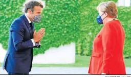 ?? CLEMENS BILAN / EFE ?? Emmanuel Macron saluda ayer a Angela Merkel en Berlín.