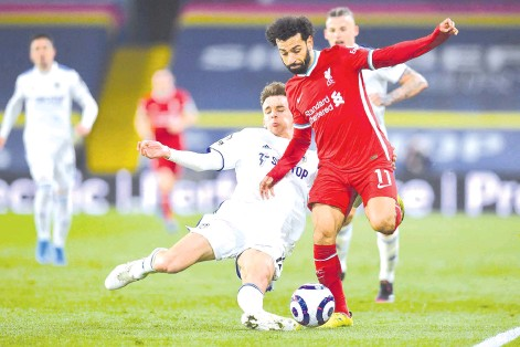 ??  ?? Leeds United's Spanish defender Diego Llorente (L) challenges Liverpool's Egyptian midfielder Mohamed Salah (R) during the English Premier League football match between Leeds United and Liverpool at Elland Road in Leeds, northern England on April 19, 2021. - AFP photo