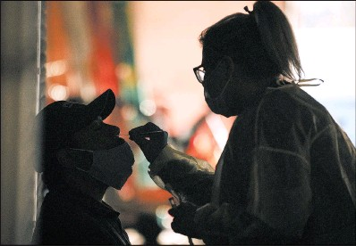 ?? TAYLOR GLASCOCK/THE NEW YORK TIMES ?? A survey found about 40% of firms with 1,001 to 5,000 workers test for COVID-19. Above, a health care worker administers a test.