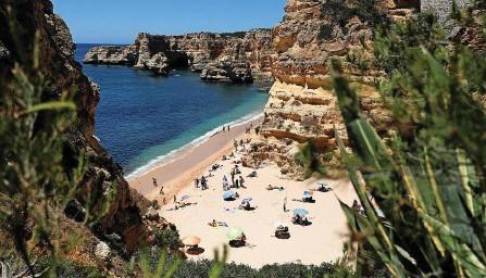 ?? REUTERS ?? Sommerferien in der Algarve (Bild: Strand von Marinha): In Portugal steigen zurzeit die Corona-Fallzahlen wieder an.