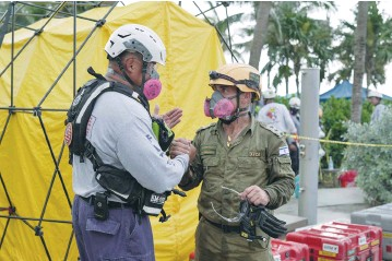 ?? (MDFD/Reuters) ?? A MEMBER of the Miami-Dade Fire Department speaks with an Israeli rescue worker at the site of the collapsed condominium complex in Surfside, Florida, earlier this month.