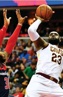 ?? (Reuters) ?? CLEVELAND CAVALIERS forward LeBron James takes an off-balance shot over Washington Wizards defender Mike Scott in the first half of the Cavs' road victory over the Wizards on Sunday night in which James finished with 20 points, 12 rebounds and 15...