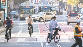 ?? Jessica Christian / The Chronicle 2020 ?? Masked cyclists navigate S.F. traffic in October near Third and Market streets.