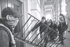 ?? JON CHERRY/GETTY IMAGES ?? A rioter uses railing to bash a door at the Capitol as others stand by filming his attempt to gain access to the building.