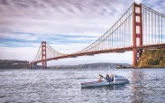 ?? Thomas Gomes / Special to the Chronicle ?? Cyril Derreumaux of Larkspur paddles outside the Golden Gate Bridge during a training session.