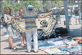 ?? KIM MANRESA ?? Un vendedor ambulante ofrece sus coloridos pareos para la playa