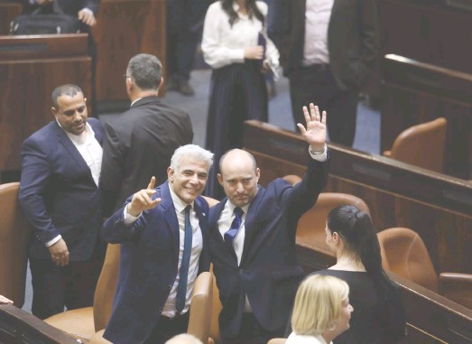 ?? (Marc Israel Sellem/The Jerusalem Post) ?? NAFTALI BENNETT and Yair Lapid celebrate the vote that brought their government to power on Sunday night. Can they keep it together?