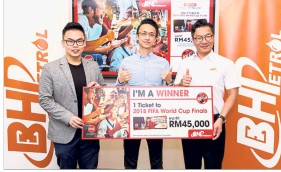 ??  ?? Lim (centre) receiving his mock prize from Coca Cola Refreshments Malaysia customer development executive Raymond Chak (left) and BHPetrol senior marketing manager Baba Tan.