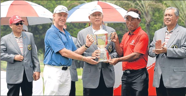 ?? Getty Images. ?? Team captains Miguel Angel Jimenez and Thongchai Jaidee are presented with the trophy by Malaysian Prime Minister Datuk Seri Najib Abdul Razak.
