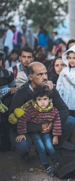 ??  ?? DESPERATE: Syrian refugees wait near to cross the border from Greece to Mac