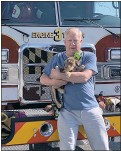 ?? CONTRIBUTED PHOTO ?? Firefighter Lennie Anthony of the Queenstown Volunteer Fire Department holds a pup evacuated from the adoption building at the animal shelter after an HVAC malfunction sparked a small fire Tuesday filling the building with smoke.