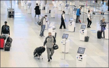 ?? THE ASSOCIATED PRESS ?? Travelersmake theirway through Minneapolis-St. Paul International Airport. ACDC official said that unless travel is curtailed, holiday-related infections could further spread through communities, reaching vulnerable individuals.