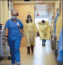 ??  ?? Nurses and medical staff make their way through the seventh-floor COVID-19 unit at East Alabama Medical Center.