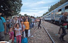 ?? MUHAMMED MUHEISEN, AP ?? In southern Hungary on Monday, migrants wait to board a train heading to the Austrian border.