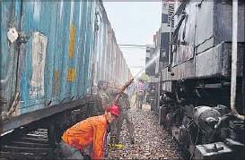 ??  ?? Firemen dousing the fire of Sabarmati Express engine at Shivpur station near Varanasi on Tuesday.