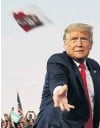 ?? PHOTO: REUTERS ?? US President Donald Trump tosses face masks into the crowd as he takes the stage for a campaign rally at Orlando Sanford International Airport in Sanford, Florida, yesterday.