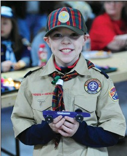 """??  ?? RIGHT: Cameron Wright, 9, a member the Webelos, Pack 2, Woonsocket, proudly holds up his """"Patriots Car' he made for the races. It has actual body shop paint and took 40 hours to construct the car, he said."""
