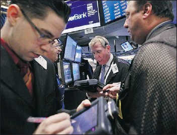 ?? — REUTERS ?? Traders work at the New York Stock Exchange on Thursday, where mixed economic news sent the Dow lower by 62 points to 13,206.59.