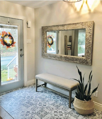 ??  ?? The home's front door entry has a new tile floor, with a bench, oversized mirror and wicker basket that brings in the European beach house vibe the couple have achieved throughout their two-bedroom house.