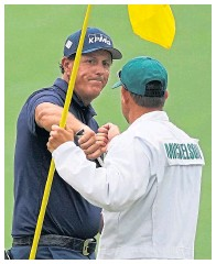 ??  ?? Phil Mickelson fist-bumps brother, and caddie, Tim