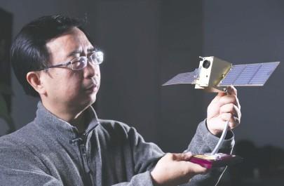 """??  ?? 中国科学技术大学潘建伟教授在办公室内与""""墨子号""""量子卫星模型合影 新华社图"""