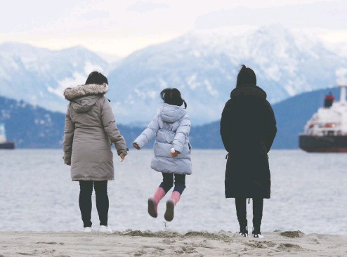 ?? JENNIFER GAUTHIER / REUTERS ?? Maria Law, who emigrated from Hong Kong with her family, looks at the mountains with her daughters from Jericho Beach in Vancouver. Like