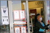 ?? LM OTERO — THE ASSOCIATED PRESS ?? A customer exits a store with a mask required sign displayed, on Tuesday in Dallas.
