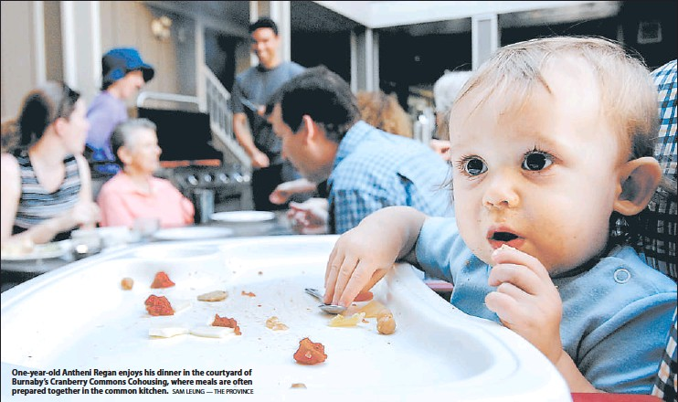 ?? SAM LEUNG — THE PROVINCE ?? — Patrick Meyer, One-year-old Antheni Regan enjoys his dinner in the courtyard of Burnaby's Cranberry Commons Cohousing, where meals are often prepared together in the common kitchen.