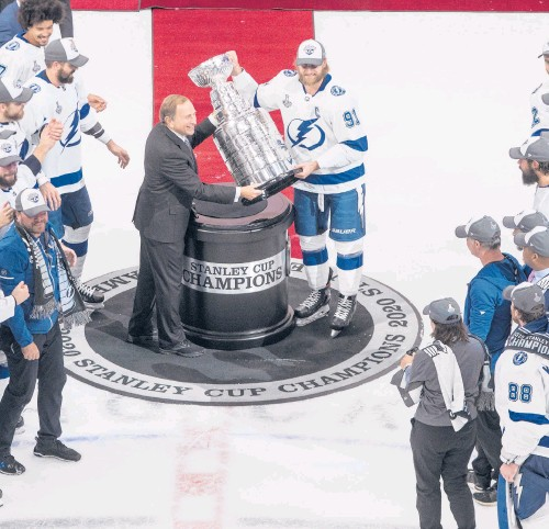?? JASON FRANSON/AP ?? Lightning's Steven Stamkos is presented the Stanley Cup from NHL commissioner Gary Bettman on Sept. 28 in Edmonton.