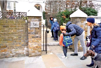??  ?? Children are dropped off by their parents at Southbank Internatio­nal School in London as schools reopen following the easing of the coronaviru­s lockdown. — AFP photo