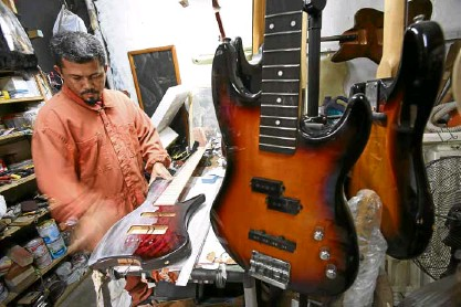 ??  ?? Aworker puts on the finishing touches to some of the guitars sold by the Guitar 1 Elegee Custom Shop