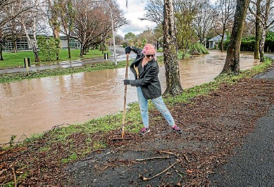 ?? PHOTO: JOHN KIRK-ANDERSON/ STUFF ?? Diana McKay cleans flood debris off Christchurch's Waimea Tce, near her home.