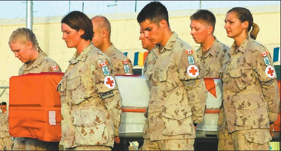 ?? GRAHAM THOMSON CANWEST NEWS SERVICE ?? Fellow combat medics bow their heads in prayer before carrying the casket of Pte. Colin Wilmot yesterday.