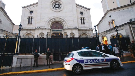 ?? (Reuters) ?? ARMED FRENCH soldiers and a police car stand in front of a Synagogue during a visit of French Interior Minister Bernard Cazeneuve after an attack at a Jewish school in Marseille in 2016.