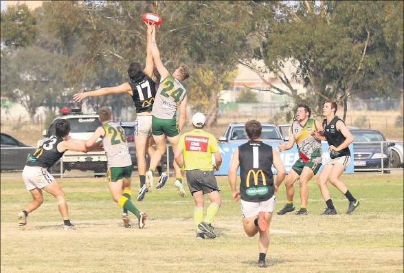 ?? Tussle: Meredith Tolliday ?? Benalla All Blacks' Will Ellis challenges Goorambat's Tom Moloney for the pill. Picture: